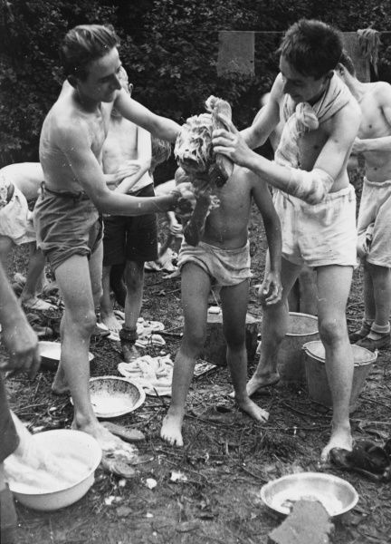 Two older boys from a Boys Club help a smaller boy to wash outdoors using soap and a small bowl of water