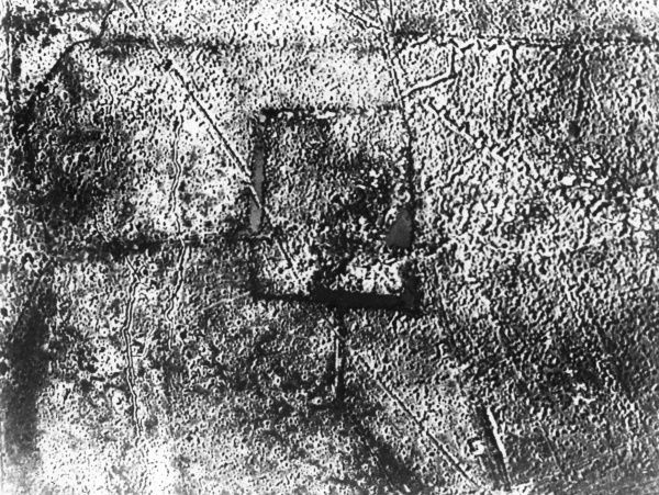 Outline of a square farm building, in an aerial photograph taken during the First World War. Date: circa 1914-1918