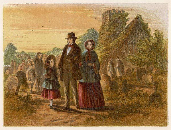 A family leave the churchyard after an evening service in an English country church