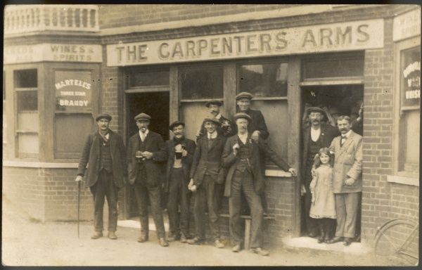 A group of drinkers assemble outside the Carpenters Arms pub for a photograph, bringing their glasses with them