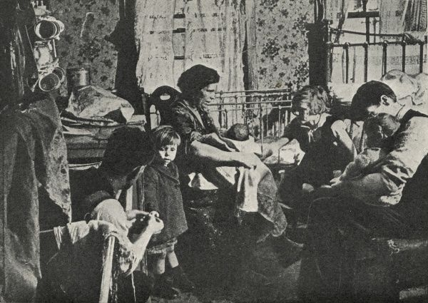 A family of seven in their cramped single-room accommodation, location unknown. Date: circa 1936