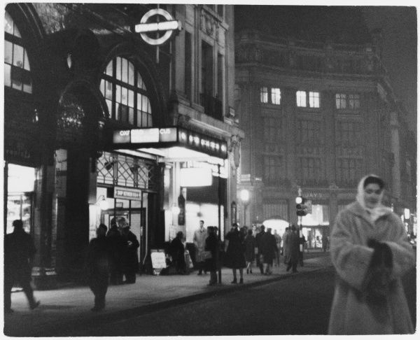 The entrance to the London underground at Oxford Circus: night scene with people passing by on the pavement and a woman crossing the street