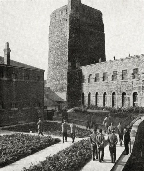 Inmates in the exercise yard at Oxford prison with St George's Tower looming behind. The prison was originally established in around 1166 as a county gaol and located within the town's Norman castle