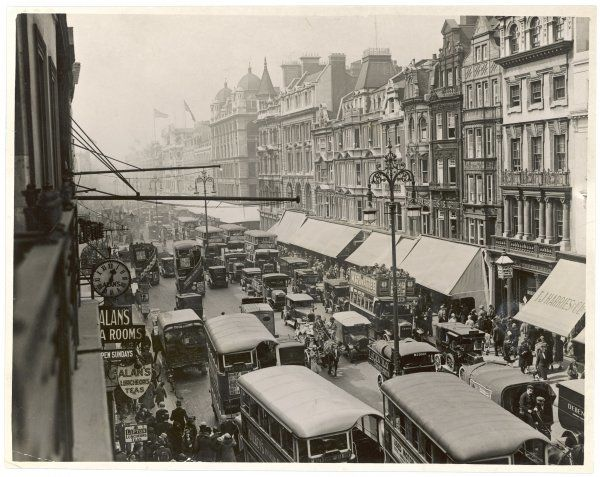 There are still horse-drawn wagons to be seen in Oxford Street among the motor buses, trucks and cabs : note the many shop blinds, rarely if ever seen here today