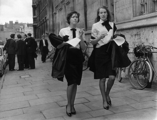 Two female students walking down the street. Date: 1960s