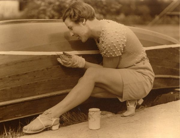 A woman in natty shorts, knitted, short-sleeved top and fishnet sandals carefully paints the bottom of a boat