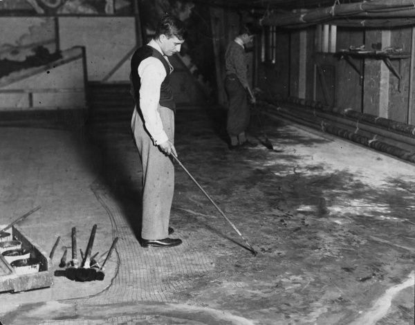 Pantomime preparations - painting scenery. The huge canvasses are laid out on the floor and the sets are painted onto them using long handle brushes. Date: 1930s
