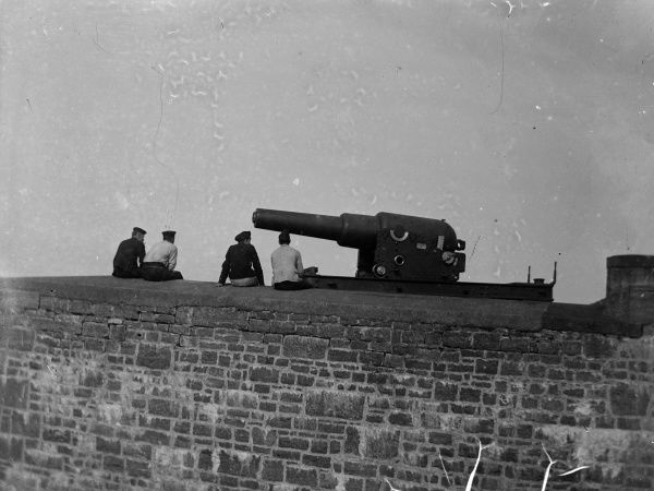 A Palliser cannon at Stack Rock Fort, on a small island off Milford Haven, Pembrokeshire, West Wales. Four men sit on the wall, relaxing. The Palliser cannon was revolutionary in its time, as it was muzzle loaded, which ensured greater stability in flight