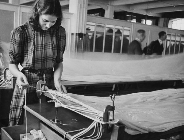 Woman working in a parachute factory threading shroud lines through the seams of the canopy during World War II