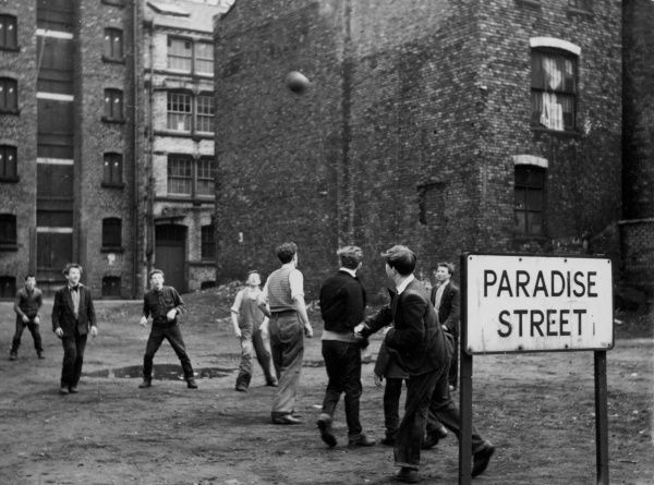 Working class lads playing street football on Paradise Street, a rough (but now regenerated) area of Liverpool, Merseyside, England. Date: 1950s
