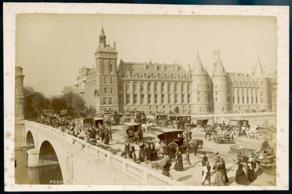 busy with people and traffic, with the Conciergerie in the background