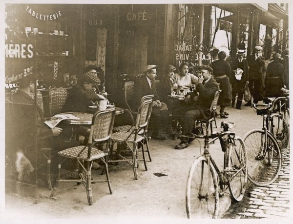 Customers enjoying themselves reading newpapers and drinking glasses of red wine outside a typical Paris Cafe