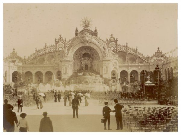 An exterior view of the Paris Exposition building, with rows of chairs outside and people and security guards milling about. There is also a 'tabac&#39