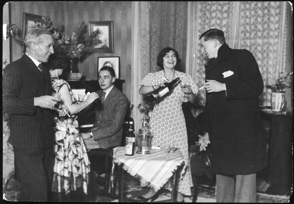 A rather jolly party at home, with lots of smoking and drinking and a rather dapper young man sitting at the piano