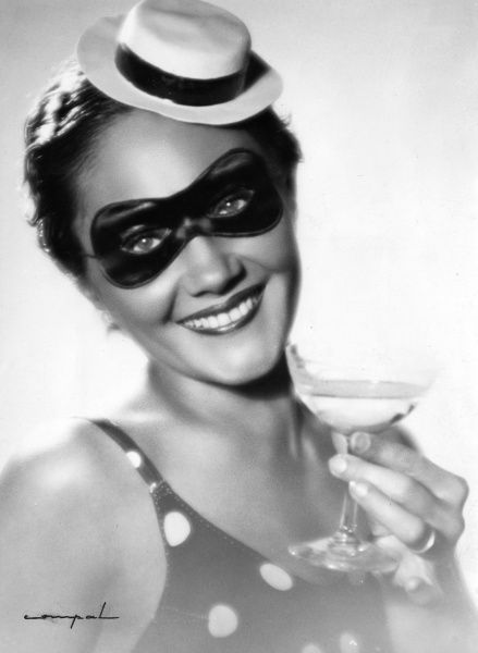 A cheeky young woman, sporting a mini boater hat, an eye mask and holding a glass of bubbly - perfect for that naughty fancy dress party! Date: 1930s