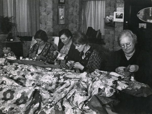 A group of ladies making patchwork quilts together. Date: 1930s