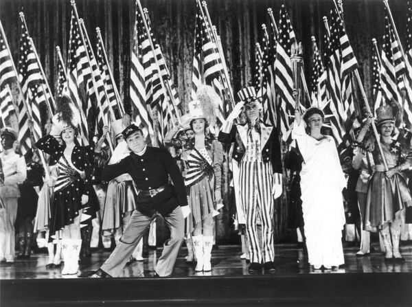 A highly patriotic stage show (possibly a musical?) featuring lines of majorette dancers holding the Star Spangled banner and figures representing a Civil War soldier, the Statue of Liberty and Uncle Sam. America's pride personified