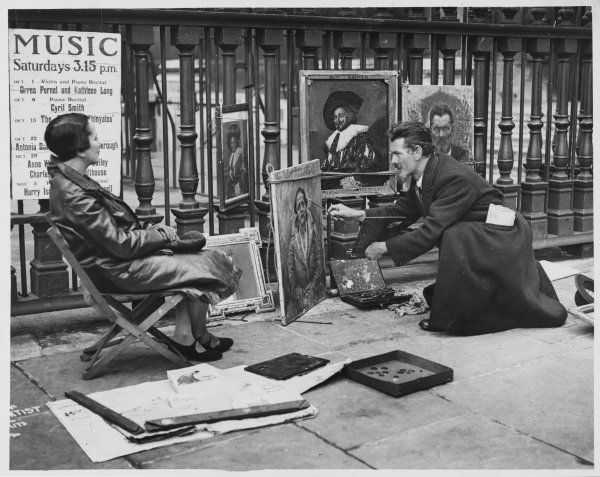 A pavement artist at St Martin-in-the-Fields, London, paints a woman's portrait; other canvases stand against the railings