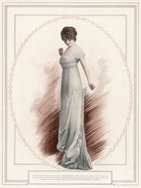 Empire revival gown in white silk voile with a high waist, square corsage, cap sleeves & a narrow trained skirt is profusely ornamented with pearls & beads