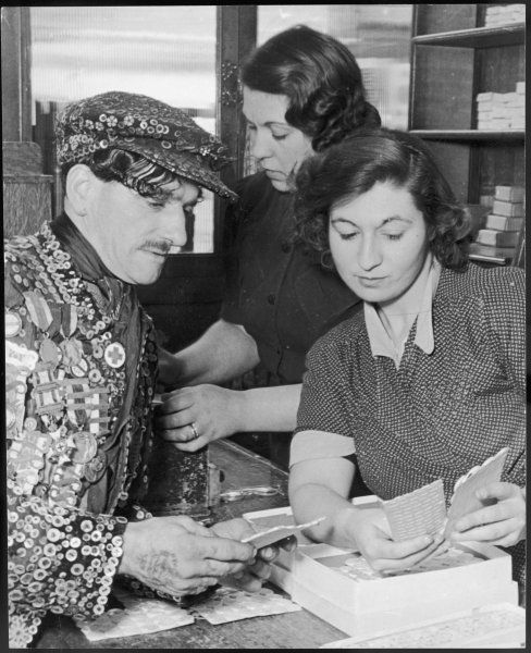 A pearly King looks at pearly buttons with two shop assistants