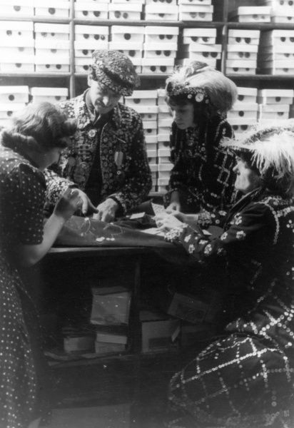 A Pearly King and Queen choosing buttons or sequins for their costumes. Date: 1930s