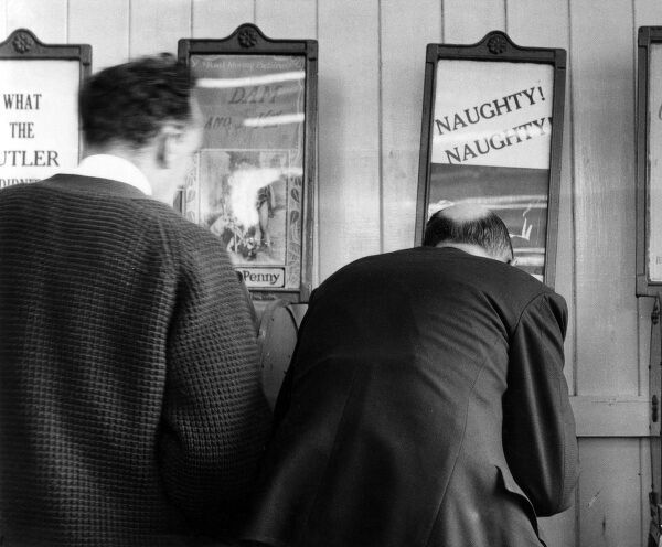Two men looking at peepshows of the What the Butler Saw variety in Brighton; one machine is advertised as 'Naughty! Naughty!' Date: 1950s