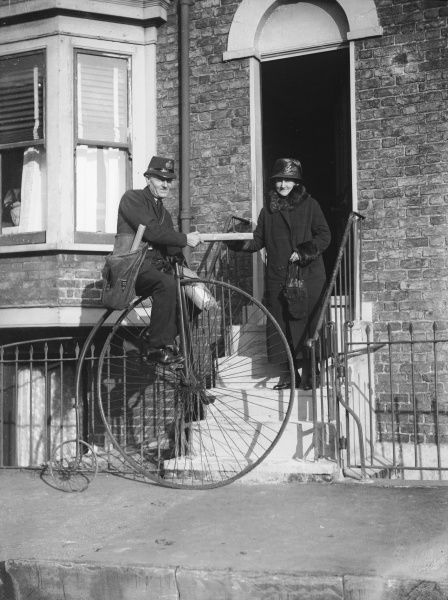 A postman on a penny farthing delivers a parcel to a woman dressed in a long coat with fur trim