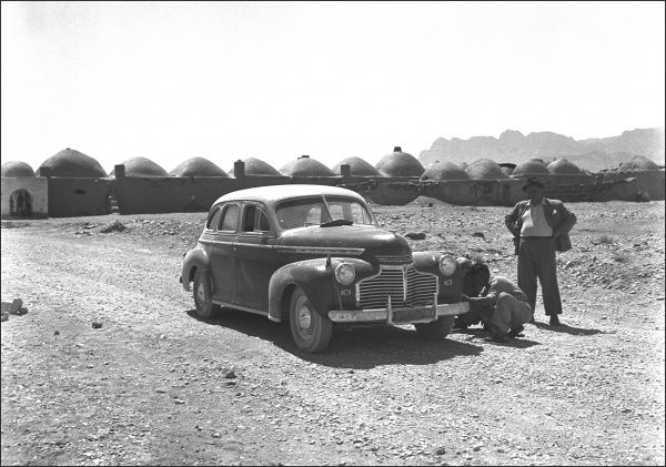 Two people and their car, somewhere in Iran, possibly having to change a tyre. In the background is a long building with many domes