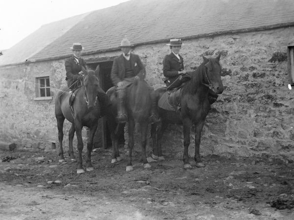 Three people, a man and two women, prepare for an outing on horseback at Tregwynt, near Granston and Fishguard, Pembrokeshire, West Wales. The women are riding sidesaddle