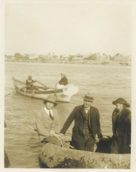 Three people -- two men and a woman -- crossing a river in a circular inflatable boat, somewhere in the Middle East. In the background are two arab men in a rowing boat