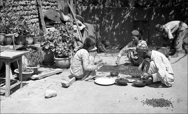 People sitting in the open air, preparing food, in Kashgar, western China. Photograph by Ralph Ponsonby Watts