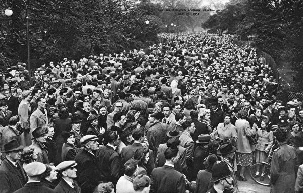 A huge crowd of people queueing for the Fun Fair in Battersea Park on a Bank Holiday, at 4pm, not put off by the cold weather. It was part of the Festival of Britain. Date: May 1951