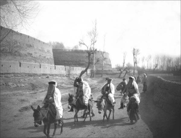 Five people riding donkeys on a road in Kashgar, western China
