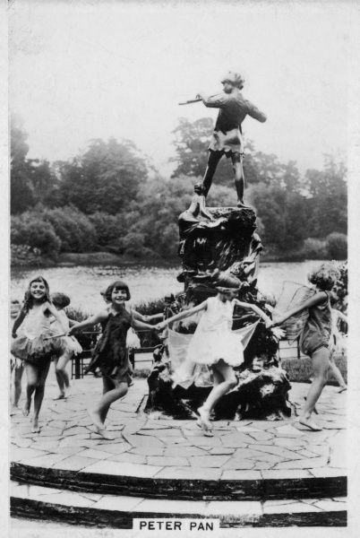 Happy children dancing in a fairy ring around Sir George Frampton's statue of Peter Pan in Kensington Gardens, which was erected on 1 May 1912