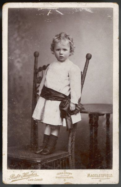 Boy in a pale coloured long sleeved frock with narrow frilled collar & cuffs & a dark coloured fringed sash round his hips, socks & shoes with a bar over the instep