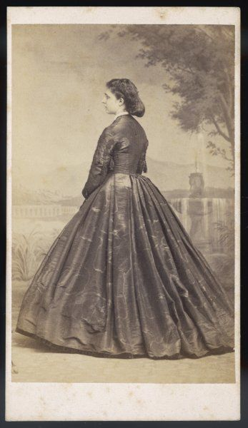 Photograph showing the rear view of dress in watered silk with the sleeves ornamented with lace, a broad band of ribbon hems the skirt. Hair: dressed in a chignon