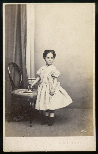 Little girl wears a short dress cut low off the shoulders in a narrow horizontal striped fabric: full skirt, ribbon trim, buttoned bodice with long pointed basques