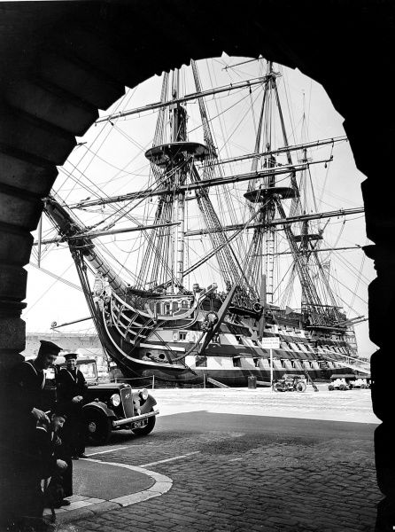 Photograph of Nelson's flagship H.M.S. Victory seen through an archway as it sits on the dock with sailors in the foreground