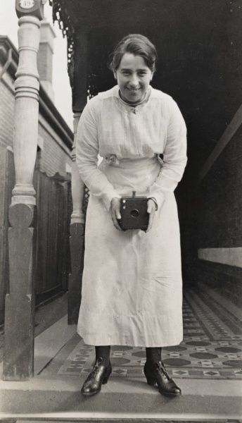 Woman taking photograph with a vintage box brownie style camera c. 1910