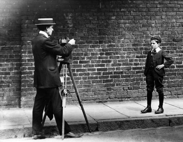A schoolboy poses on a pavement for a 'While-u- Wait' street photographer, England. Date: early 1900s