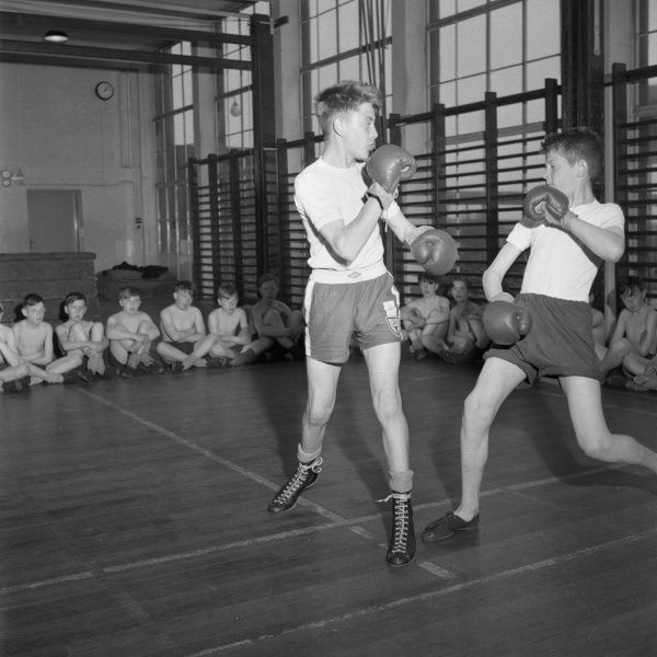 At a secondary school in Stoke on Trent, England, two boys box in front of their class mates, part of their physical education