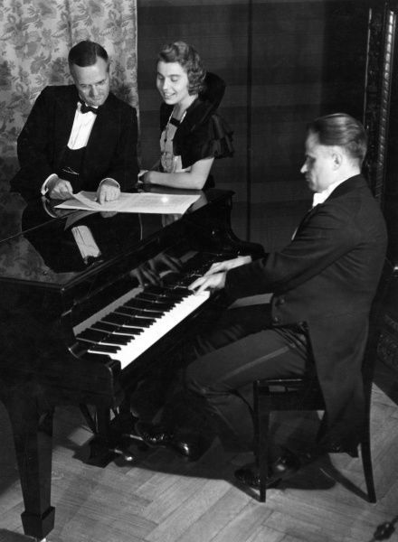 A stylish young couple get ready to sing a duet beside the piano, while a smart pianist tickles the ivories.. Date: 1930s