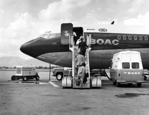 Passengers boarding a BOAC 707 aeroplane (as it is being refuelled) at Piarco Airport, Trinidad, West Indies. Date: 1960s