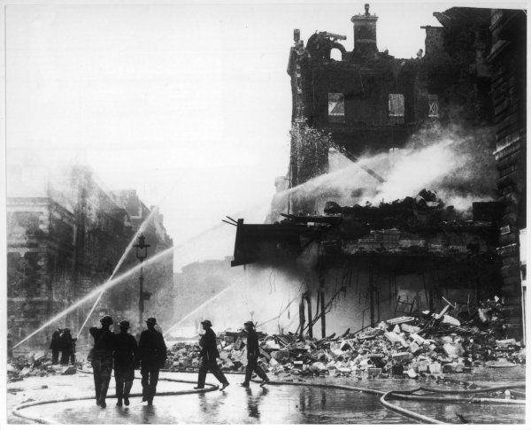 The aftermath of an air raid on Piccadilly, central London; firefighters hosing the smouldering remains of damaged buildings