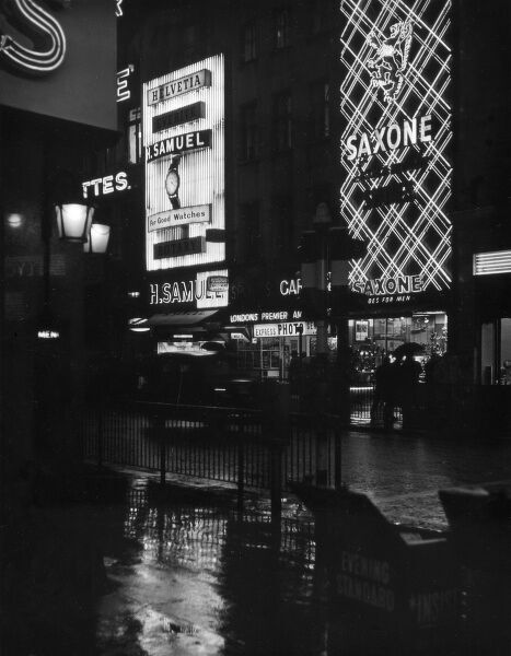 Neon signs and all the bright lights of the city at night, a familiar sight at Piccadilly Circus, central London. Date: 1950s