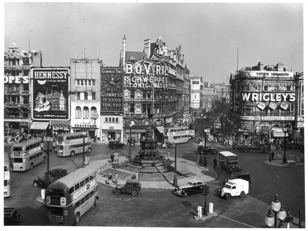 Piccadilly Circus, London, with buses rounding the statue of Eros, and advertising hoardings featuring Wrigley's, Bovril, and Guinness