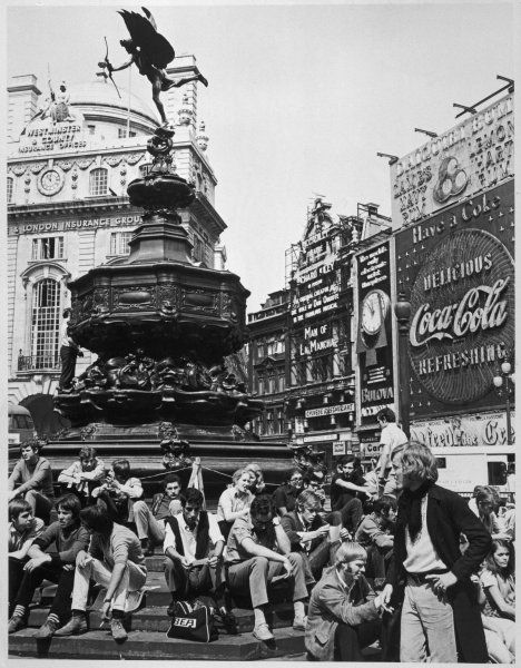 Young people enjoying the sunshine at Piccadilly Circus under Eros