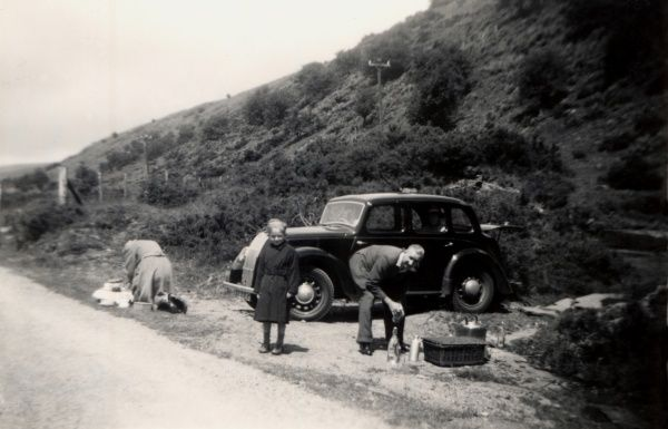 A family stops for a roadside picnic alongside their Morris 8 E-series 4-door Six Light