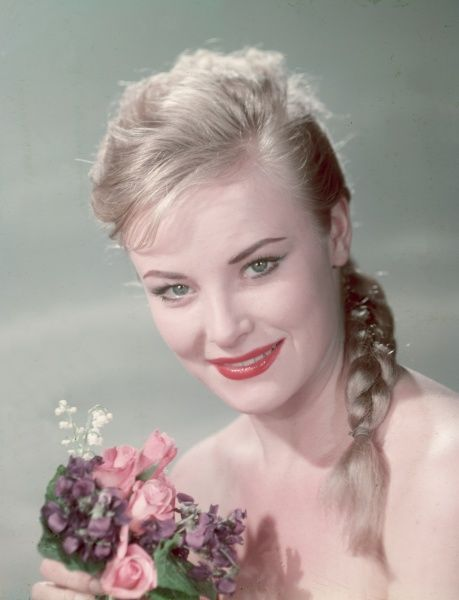 Pretty blonde woman with a plait holds a bunch of flowers, which include pink roses, against her bare chest