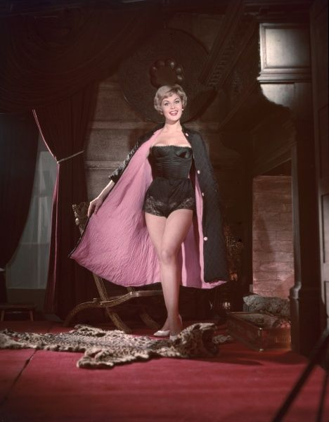 Pin-up with a beaming smile, poses in a pink lined black cape, black corselette & lace knickers, in a rich interior complete with a leopard skin rug with the head on!